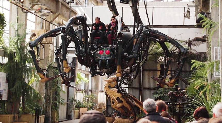 two people riding giant mechanical spider carousel